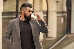 最佳的时候喝咖啡 有胡子的人饮用的早晨咖啡 在拿着外带的咖啡的行家样式的商人 图库摄影