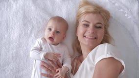 最佳的片刻从生活,爱的愉快的年轻母亲拥抱并且亲吻毯子的一个新出生的在照相机的女儿和神色 股票录像