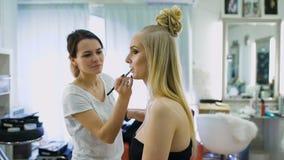 最后一笔 在美丽的金发碧眼的女人的沙龙做构成 化妆师绘她的嘴唇,增加数额  影视素材