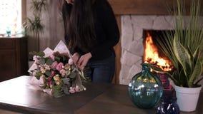 最后的接触 女性卖花人领带在她的准备好花束的丝带在桃红色,淡色 享受她的工作 慢 股票录像