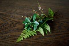 最后绿色植物的美丽的秋天花束木表面上的 越橘叶子、蕨叶子和石南花枝杈 r 免版税图库摄影