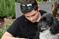 最好的朋友、十几岁的男孩和他的丑角长卷毛狗 免版税图库摄影