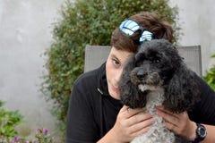 最好的朋友、十几岁的男孩和他的丑角长卷毛狗 免版税库存照片