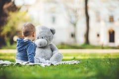 最好的朋友 使用户外与他的玩具熊的逗人喜爱的小孩 免版税图库摄影