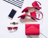 最小的套的平的位置女性辅助部件:金黄手表,与脚腕皮带,女用无带提包,流动pho的红色中间脚跟凉鞋 免版税图库摄影