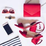 最小的套的平的位置女性辅助部件:金黄手表,与脚腕皮带,女用无带提包,流动pho的红色中间脚跟凉鞋 免版税库存照片