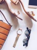 最小的套的平的位置女性辅助部件:金黄手表,与脚腕皮带,皮革扣袋子的中间脚跟凉鞋,流动 免版税库存照片