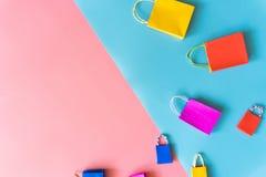 最小的购物网上概念,五颜六色的纸购物袋从漂浮拷贝空间的桃红色和蓝色背景去下来 免版税库存图片