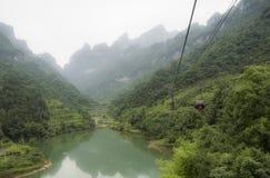 最长的空中览绳在世界上,与湖的风景视图,山、绿色森林和薄雾-天门山,天堂` 免版税库存照片