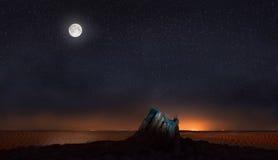 月亮和星在石头在沙漠 免版税库存图片