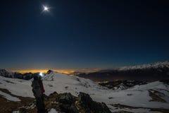 月亮和满天星斗的天空,在阿尔卑斯的雪,全天相镜头 猎户星座星座、猎户星座中一等星和Sirio 长的曝光弄脏了两个远足者l 库存照片