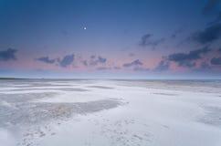 满月和日出天空在沙子靠岸 免版税库存照片