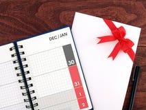 12月和1月日期在日历日志计划者页和贺卡白色信封与红色丝带在黑褐色鞠躬 免版税库存图片