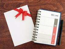 12月和1月日期在日历日志计划者页和贺卡白色信封与红色丝带在黑褐色鞠躬 图库摄影