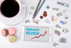 2月回顾,企业概念 手机和咖啡杯在白色办公桌上 库存照片