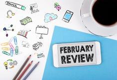 2月回顾 手机和咖啡杯在白色办公桌上 库存照片