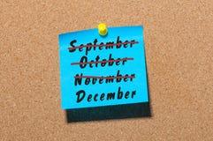 12月开始和底概念11月, 10月, 9月,写在蓝纸被别住在布告牌 前夕 免版税库存图片