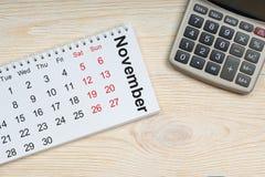 11月日历,在木桌上的计算器 免版税图库摄影