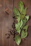 月桂叶和香料在一张木桌上 免版税库存图片