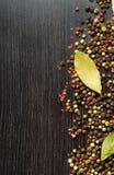 月桂树在木桌留下混合四胡椒 库存图片
