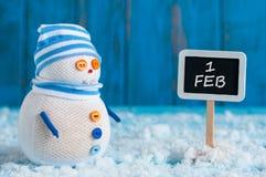 2月的1日路标和雪人站立近的方向标 愉快的冬天明信片 免版税库存照片
