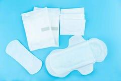 月经带和吸收剂板料在蓝色背景 免版税库存图片