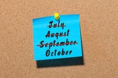 10月起点概念被写在被别住的纸在黄柏布告牌背景 触击7月, 8月, 9月 库存照片