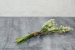 5月铃兰精美芬芳花束栓与在黑暗的具体背景的黄麻绳子 图库摄影