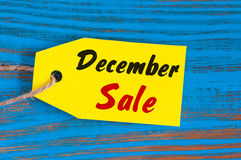 12月销售,在蓝色木背景的价牌 伊芙、圣诞节和新年打折概念 免版税库存照片