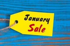 1月销售,在蓝色木背景的价牌 库存图片