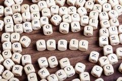4月,信件把词切成小方块 免版税库存图片