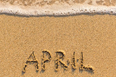 4月-在与软的波浪的沙子海滩得出的词 免版税库存图片