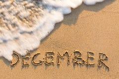 12月-在沙子海滩得出的词 库存照片