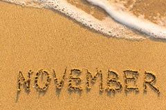 11月-在沙子海滩的题字 库存图片