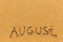 8月-在金沙子海滩的词题字 免版税库存照片