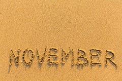 11月-在金沙子海滩的词题字 免版税库存图片
