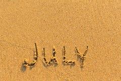 7月-在金沙子海滩的词题字 免版税图库摄影