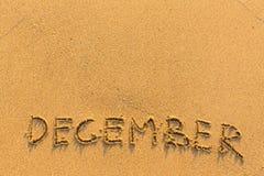 12月-在金沙子海滩的词题字 免版税库存照片