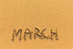 3月-在金沙子海滩的词题字 免版税库存图片