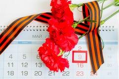 5月9日与三支红色康乃馨的背景和在日历的圣乔治丝带与5月9日日期 免版税库存图片