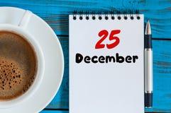 12月25日伊芙圣诞节 天25月,在工作场所背景的日历与早晨咖啡杯 概念新年度 免版税库存照片