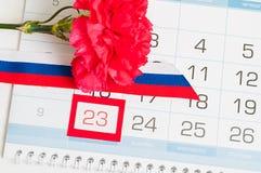 2月23日卡片 红色康乃馨、俄国三色旗子和日历与被构筑的日期2月23日 免版税库存照片