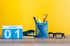 4月1日在桌上的天1 4月月,日历有黄色背景和办公室或者学校用品 春天…上升了叶子,自然本底 免版税库存照片