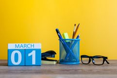 3月1日在桌上的天1行军月,日历有黄色背景和办公室或者学校用品 春天…上升了叶子,自然本底 免版税库存照片