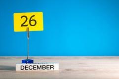 12月26日大模型 天26 12月月,在蓝色背景的日历 花雪时间冬天 文本的空的空间 图库摄影