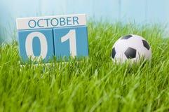 10月1日天1月,在绿草背景的颜色日历与球 秋天时间 橄榄球和足球戏剧 免版税库存图片