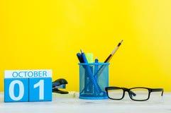 10月1日天1月,在老师的木颜色日历或学生桌,黄色背景 秋天时间 空 免版税图库摄影