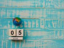 6月05日木块日历地球和听诊器在蓝色木头 免版税图库摄影