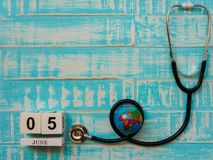 6月05日木块日历地球和听诊器在蓝色木头 图库摄影