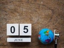 6月05日木日历块、地球和听诊器在木t 免版税库存照片
